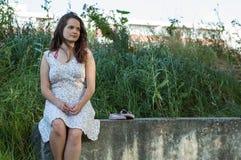 La muchacha se sienta en un bloque de cemento fotografía de archivo libre de regalías