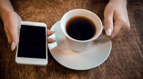La muchacha se sienta en un caf? y sostiene una taza de t? y un tel?fono en sus manos, esperando una llamada fotografía de archivo
