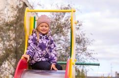 la muchacha se sienta en un children& x27; diapositiva de s en la yarda Fotografía de archivo