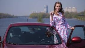 La muchacha se sienta en un coche rojo, abre la puerta, subidas fuera del coche y muestra las llaves 4K MES lento almacen de metraje de vídeo