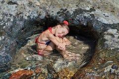 La muchacha se sienta en una bañera natural Foto de archivo