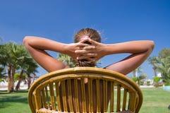 La muchacha se sienta en una butaca en una hierba Fotos de archivo