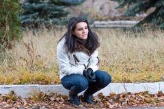 La muchacha se sienta en una chaqueta en el otoño en parque Imagenes de archivo