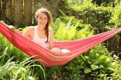 La muchacha se sienta en una hamaca Imagenes de archivo