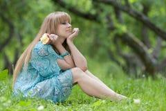 La muchacha se sienta en una hierba con una manzana Imagen de archivo