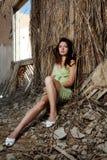 La muchacha se sienta en una pared de la casa Imagenes de archivo