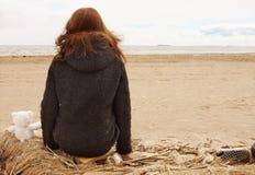 La muchacha se sienta en una red de pesca y mira el agua de la bahía, al lado de un oso de peluche con ella detrás Fotos de archivo