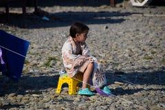 La muchacha se sienta en una silla cerca de una tienda envuelta en una manta foto de archivo libre de regalías