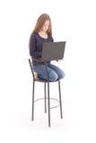 La muchacha se sienta en una silla y sostener un ordenador portátil Fotos de archivo