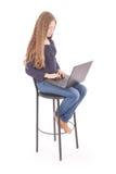 La muchacha se sienta en una silla y sostener un ordenador portátil Imagen de archivo