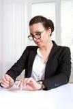 La muchacha se sienta en una tabla que mira sobre sus vidrios Foto de archivo libre de regalías