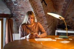 La muchacha se sienta en una tabla que mira un smartphone del vintage Fotografía de archivo libre de regalías