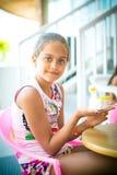 La muchacha se sienta en una tabla y adorna la estatuilla de la arcilla Foto de archivo libre de regalías