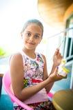 La muchacha se sienta en una tabla y adorna la estatuilla de la arcilla Fotografía de archivo