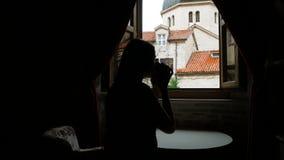La muchacha se sienta en la ventana en la mesa redonda en el hotel metrajes
