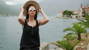 La muchacha se sienta por el agua en un sombrero de paja y en un vestido negro metrajes