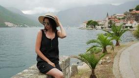La muchacha se sienta por el agua en un sombrero de paja y en un vestido negro almacen de metraje de vídeo