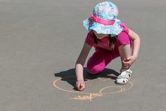 La muchacha se sienta y dibuja con tiza en el asfalto Apple Imagen de archivo