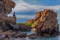 La muchacha se sienta y teniendo resto en roca grande en la montaña foto de archivo