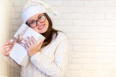 La muchacha se sostiene en sus manos y abre un regalo de oro de la Navidad L Foto de archivo
