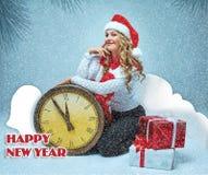 La muchacha se vistió en el sombrero de santa que se sostenía con las decoraciones de una Navidad fotografía de archivo libre de regalías