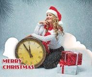 La muchacha se vistió en el sombrero de santa que se sostenía con las decoraciones de una Navidad fotos de archivo