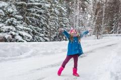 La muchacha se vistió en una capa azul y un sombrero rosado y patea tiros nieva para arriba Imagen de archivo