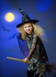 La muchacha se vistió para arriba como bruja en escoba del vuelo de la noche Fotografía de archivo