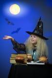 La muchacha se vistió para arriba como bruja en la noche que hacía magia Foto de archivo libre de regalías