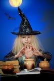 La muchacha se vistió para arriba como bruja en la noche que hacía magia Imagen de archivo libre de regalías