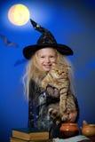 La muchacha se vistió para arriba como bruja en noche con el gato Fotos de archivo