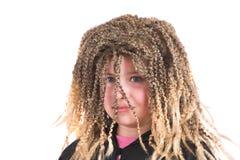 La muchacha se vistió para arriba con una peluca divertida del rasta Fotografía de archivo