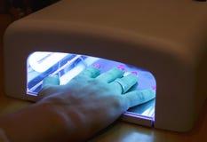 La muchacha seca al esmalte de uñas Foto de archivo