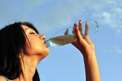 La muchacha sedienta bebe la agua fría en día caliente Fotos de archivo libres de regalías