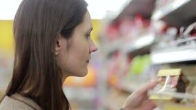 La muchacha selecciona el artículo en los estantes en la tienda metrajes