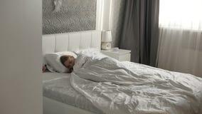 La muchacha semidesnuda está mintiendo en la cama almacen de metraje de vídeo