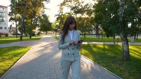 La muchacha sensual en un traje de negocios ligero va a trabajar mujer de negocios hermosa que camina a lo largo del callejón en  almacen de metraje de vídeo