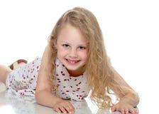 La muchacha sentada abajo en el piso Imagen de archivo libre de regalías