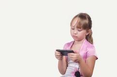 La muchacha seria en un vestido elegante juega el teléfono Imagen de archivo libre de regalías
