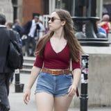 La muchacha seria hermosa con el pelo largo en una camisa roja y pantalones cortos azules cruza el camino cerca del cuadrado de L Fotografía de archivo