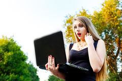 La muchacha seria hermosa mira un ordenador portátil Fotos de archivo libres de regalías