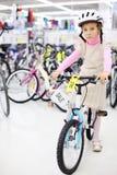 La muchacha seria se sienta en la bicicleta brillante y mira Fotos de archivo