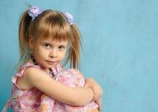 La muchacha sienta el abarcamiento de rodillas. Fotos de archivo