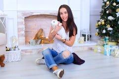La muchacha sienta la sonrisa y la presentación con el conejo en estudio adornado Fotos de archivo libres de regalías