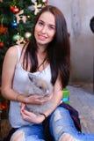 La muchacha sienta la sonrisa y la presentación con el conejo en estudio adornado Imágenes de archivo libres de regalías