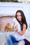 La muchacha sienta la sonrisa y la presentación con el conejo en estudio adornado Foto de archivo