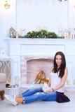 La muchacha sienta la sonrisa y la presentación con el conejo en estudio adornado Imagen de archivo