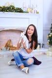 La muchacha sienta la sonrisa y la presentación con el conejo en estudio adornado Fotos de archivo