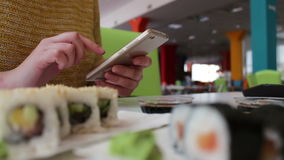 La muchacha sienta mecanografiar en un smartphone y de comunicación con el interlocutor en el café en la tabla es el sushi, japon almacen de metraje de vídeo