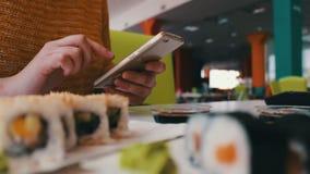 La muchacha sienta mecanografiar en un smartphone y de comunicación con el interlocutor en el café en la tabla es el sushi, japon metrajes